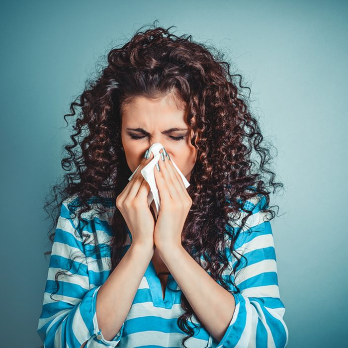 Closeup portrait of woman sneezing or using towel to wipe snot from her nose