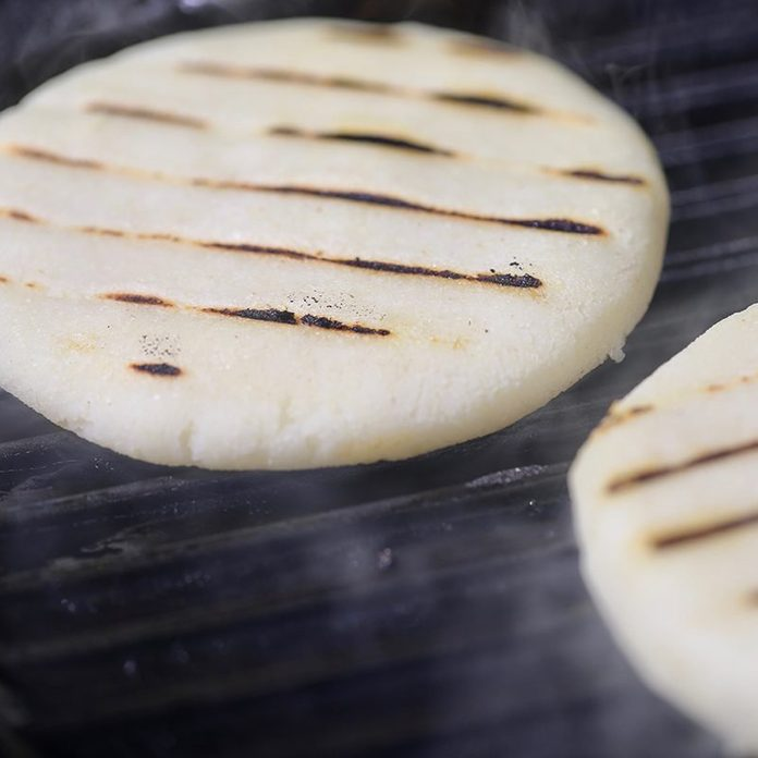 Two arepas on a grill.