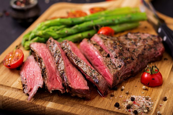 Juicy steak rare beef with spices on a wooden board and garnish of asparagus.