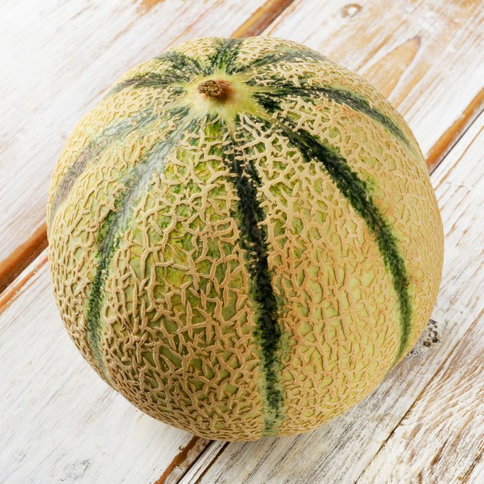 Whole melon on a wooden background.