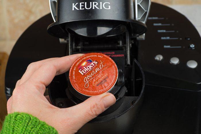 ATLANTA, GA -- FEB 14, 2014: Close-up of woman inserting single-serve K-cup Foldger's coffee into a Keurig coffee maker. ; Shutterstock ID 176711798; Job (TFH, TOH, RD, BNB, CWM, CM): Taste of Home