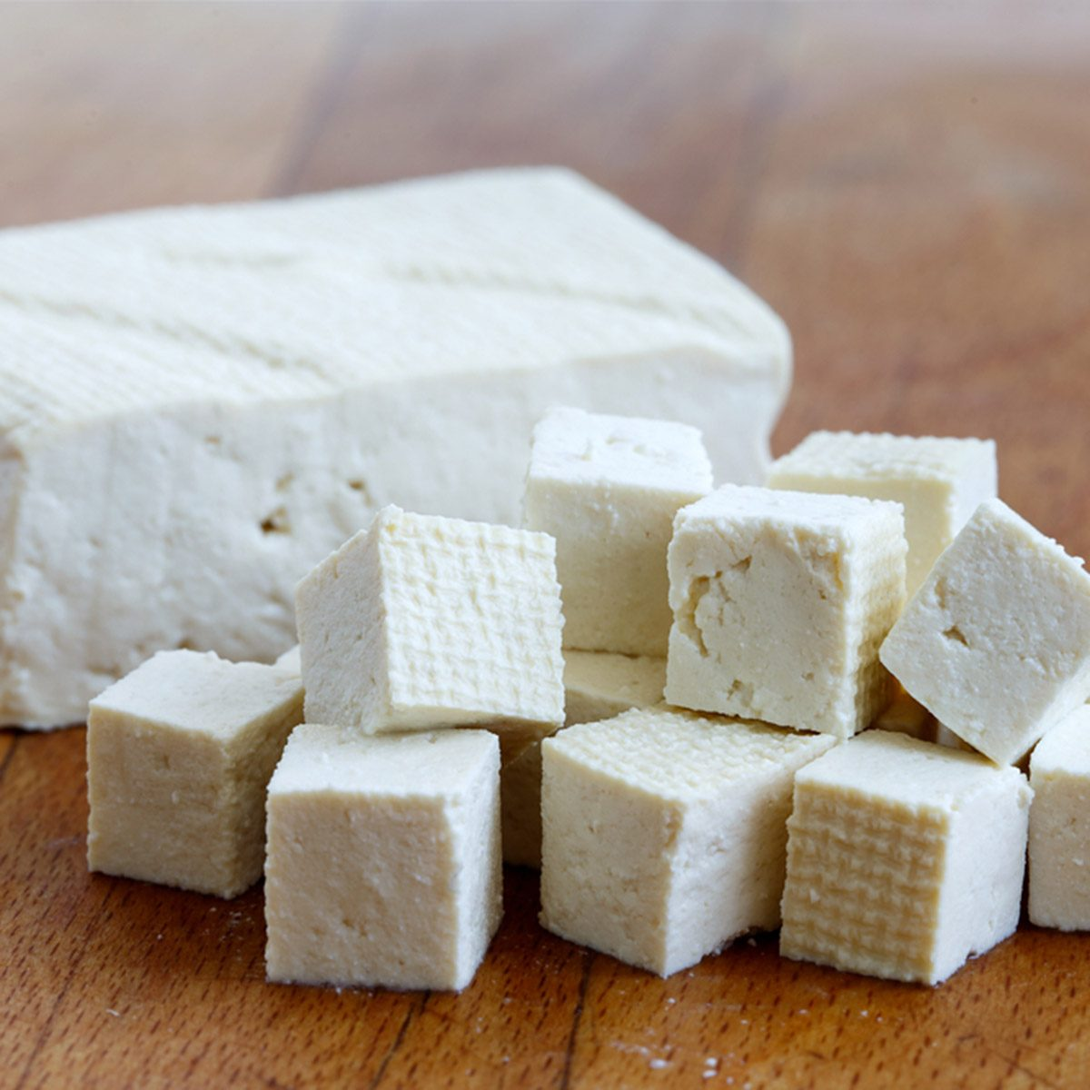 Single block of white tofu with cut tofu cubes on wooden chopping board.