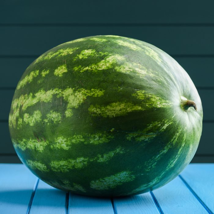 Big whole striped watermelon on blue background