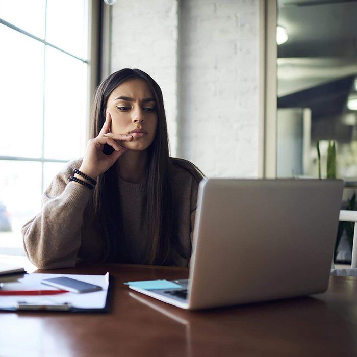 Thoughtful brunette student watching training webinar