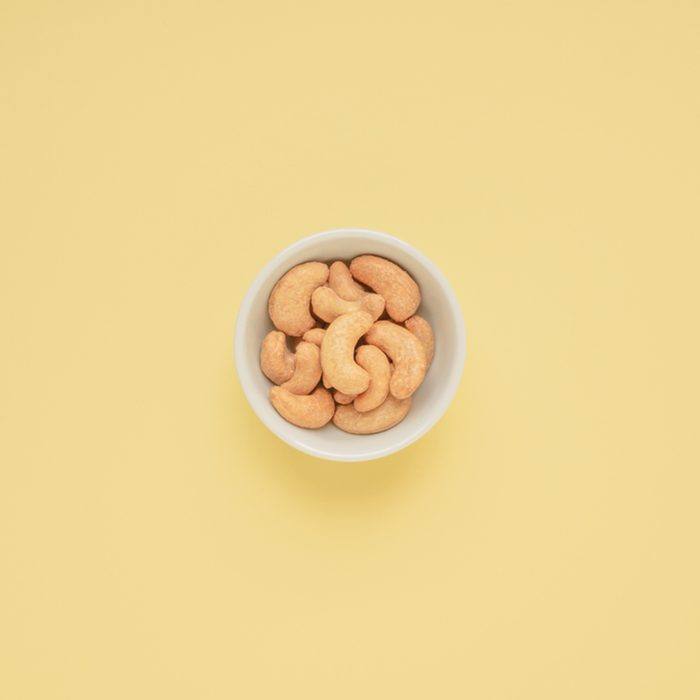 Cashew nuts in white cup on yellow background and copy space