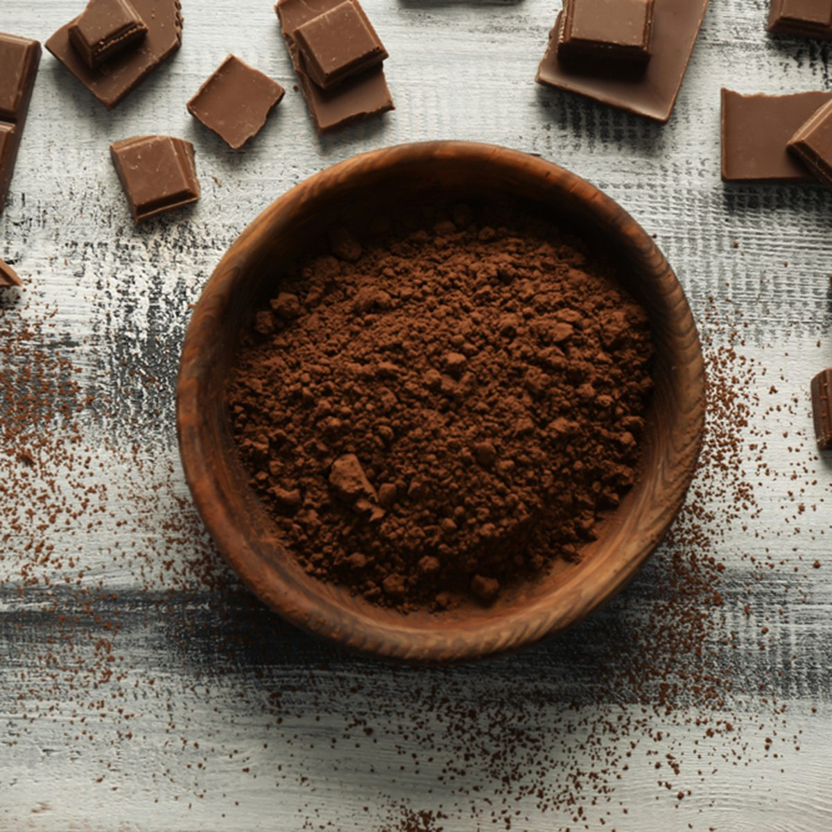 Bowl with cocoa powder and tasty chocolate on wooden background