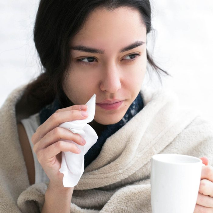 Young woman sick in bed with temperature drinks hot
