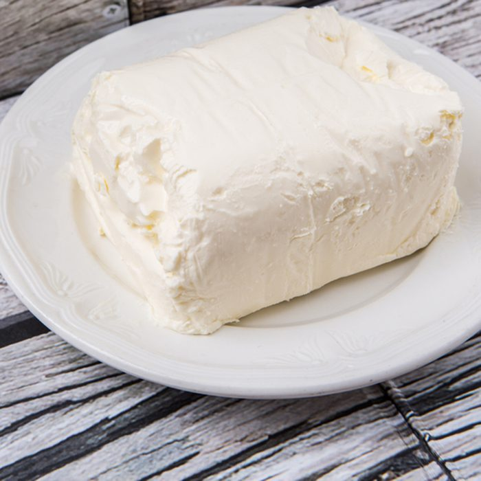 A block of cream cheese on a white plate over weathered wooden background