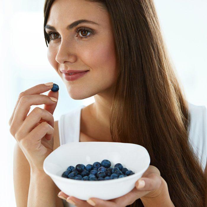 Portrait Of Attractive Smiling Girl Eating Ripe Fresh Juicy Tasty Sweet Organic Blueberries