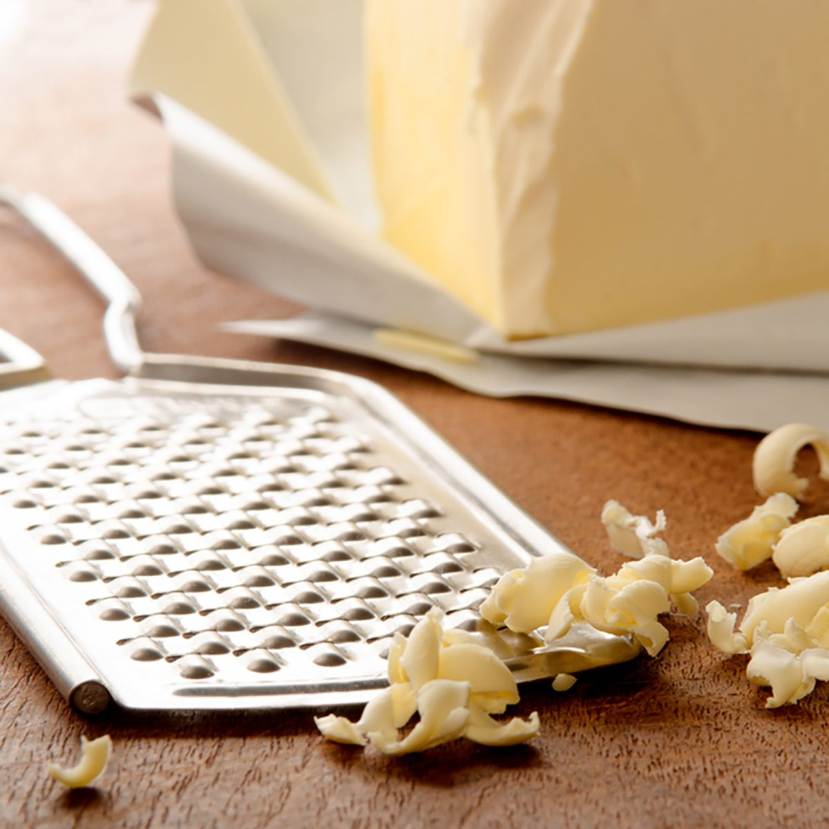 grated butter and grater on wooden board