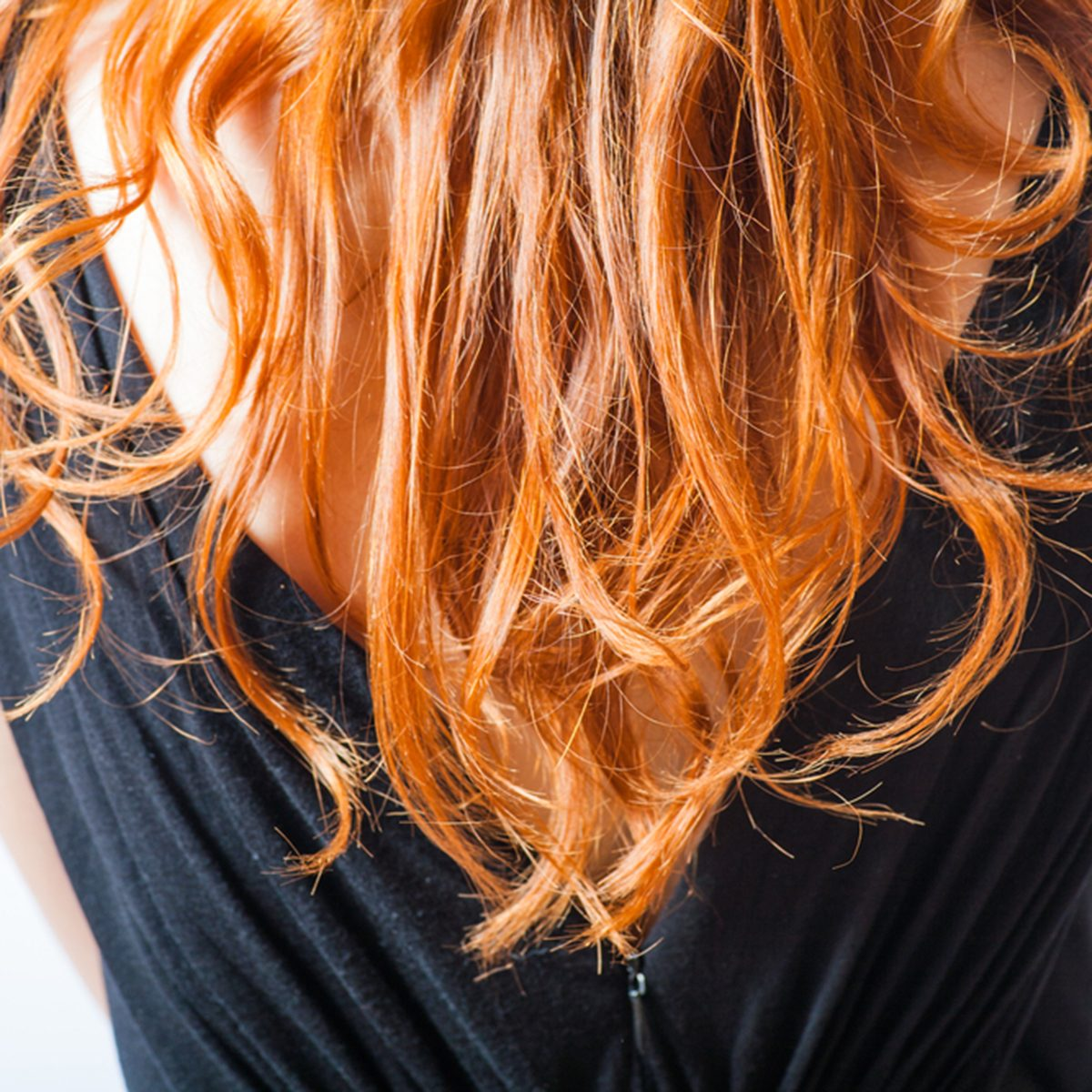 rear closeup view of the shoulders of red haired (carrot-top) female weared black dress