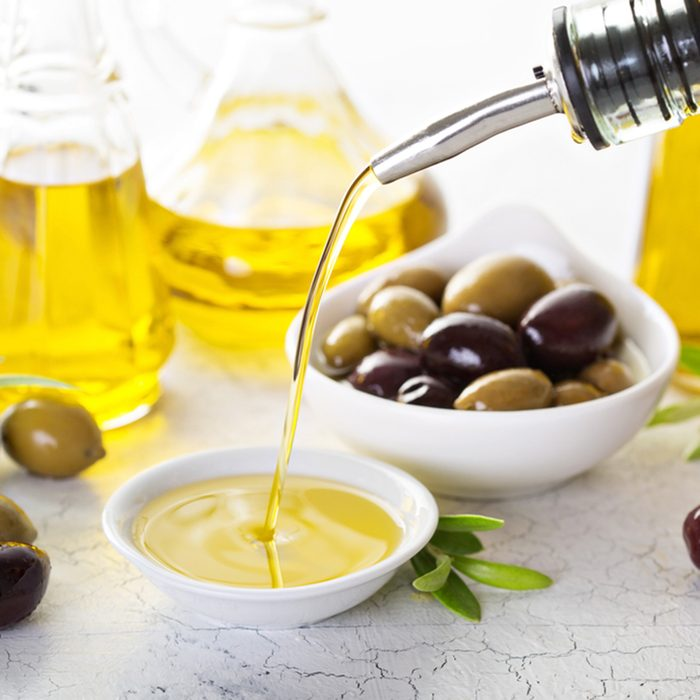 Olive oil in vintage bottles and small bowl