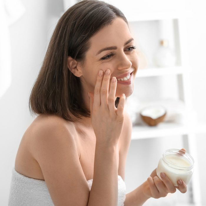 Young woman applying coconut oil in bathroom