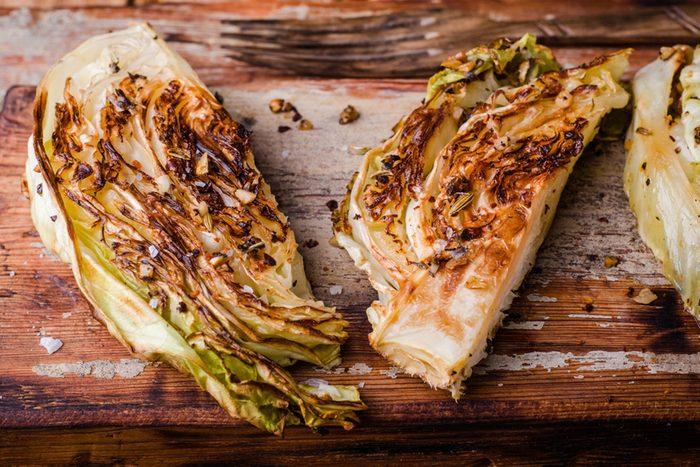 Vegan roasted cabbage steaks on wooden vintage background.