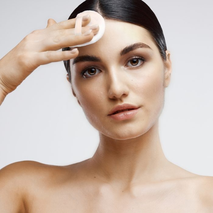 A beautiful woman wipes her face with a cotton pad and bare shoulders