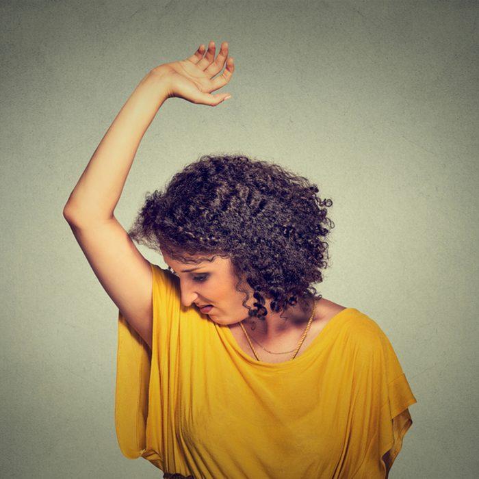 Closeup portrait young woman, smelling, sniffing her wet armpit