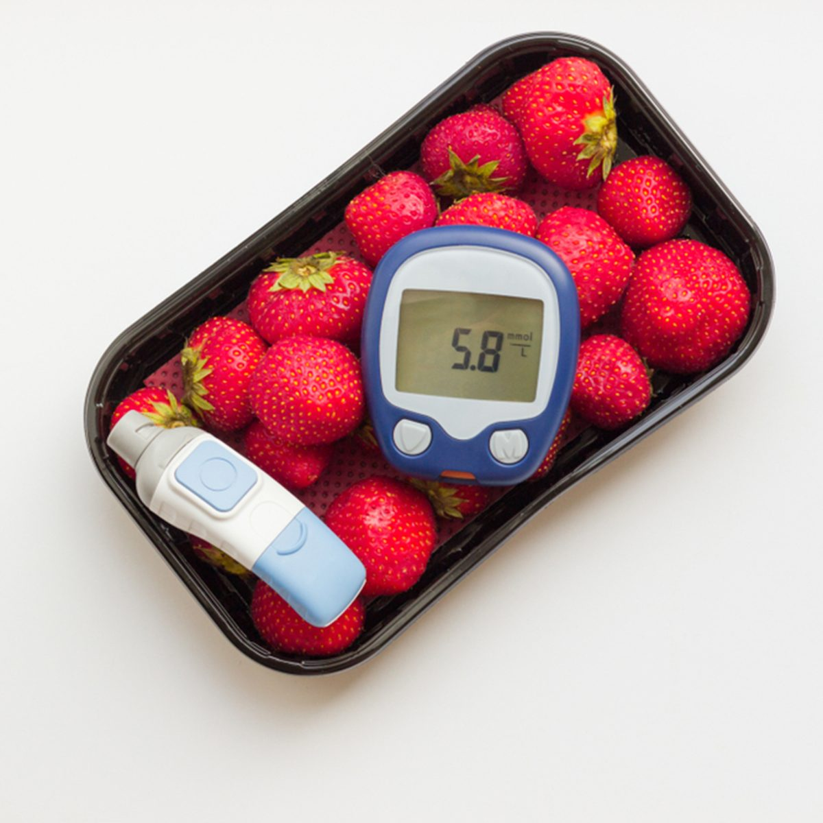 the meter shows normal sugar levels 5,8 mmol/l on background of strawberry.