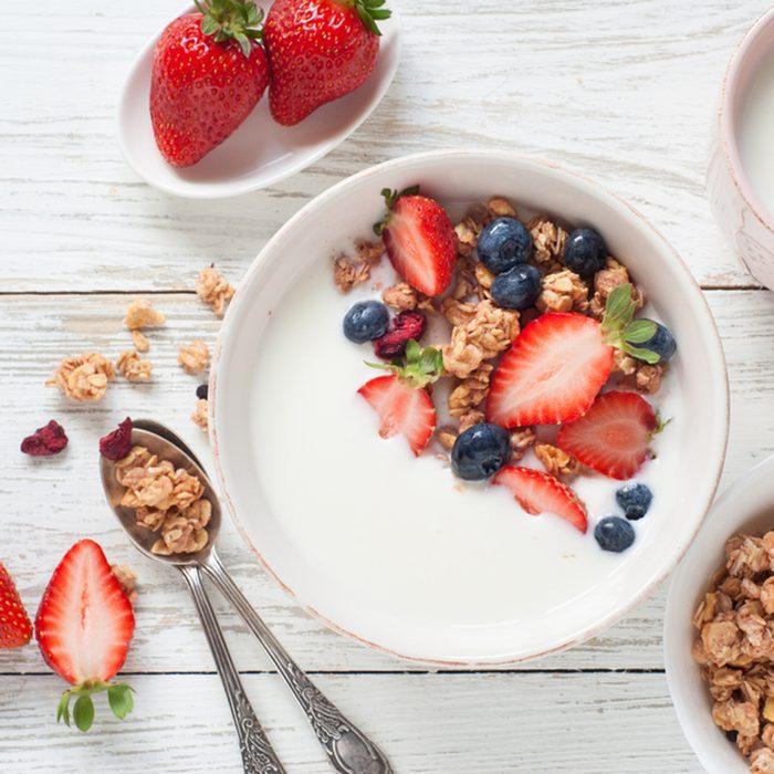 Yogurt with granola, strawberry and blueberry.