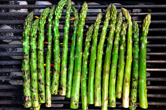 Spears of asparagus on a charcoal grill.