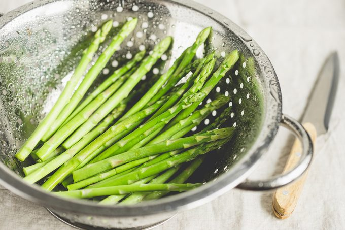 Washed asparagus in a metal collander.