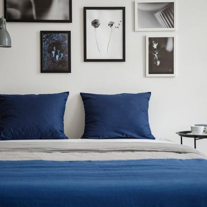 Blue bed with framed photos overhead
