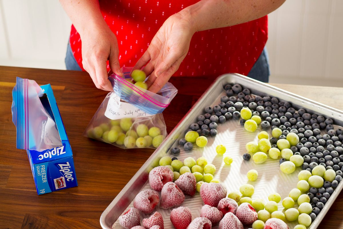 A person putting frozen berries and grapes into a freezer bag.