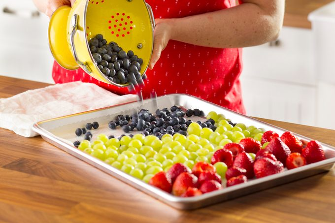 A person transferring just-washed berries and grapes from a collander to a baking sheet.