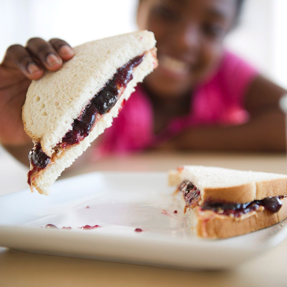 Girl eating peanut butter and jelly sandwich