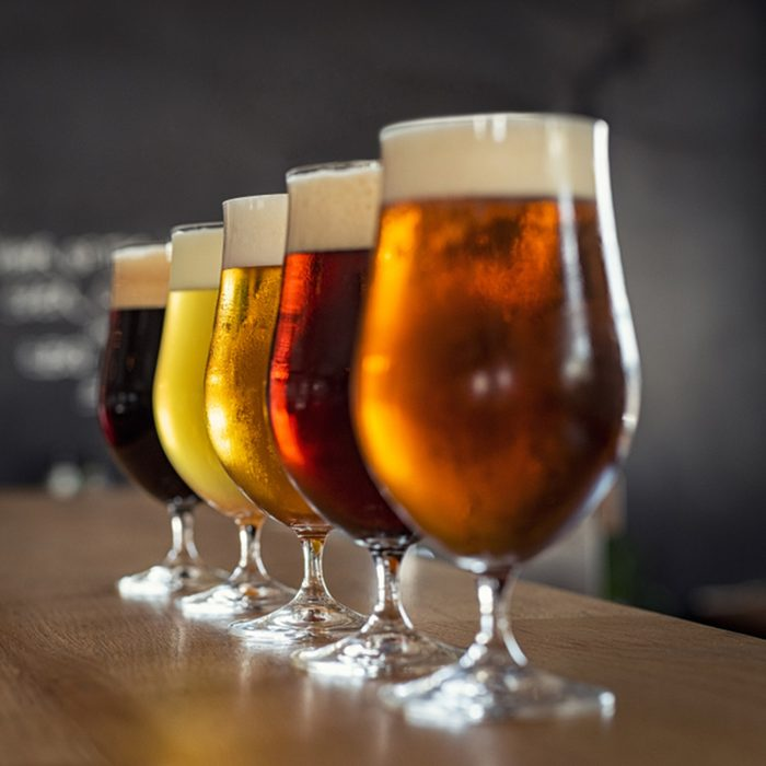 Glasses with different sorts of craft beer on wooden bar.