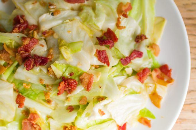 Asia food, Stir fried cabbage with fish sauce and crispy bacon on wooden table