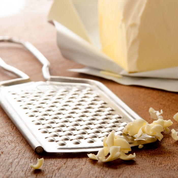 grated butter and grater on wooden board; Shutterstock ID 398422966