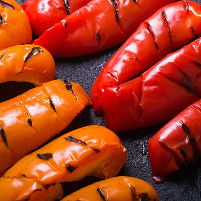 Orange and red grilled peppers on black stone