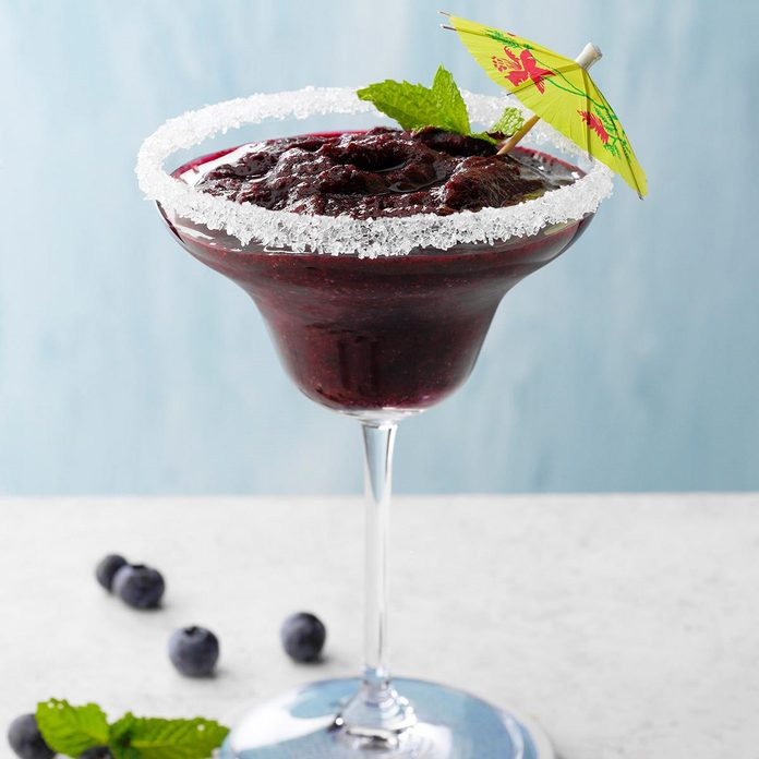 A homemade blueberry-mint frozen margarita in a glass with a salted rim and a decorative umbrella.