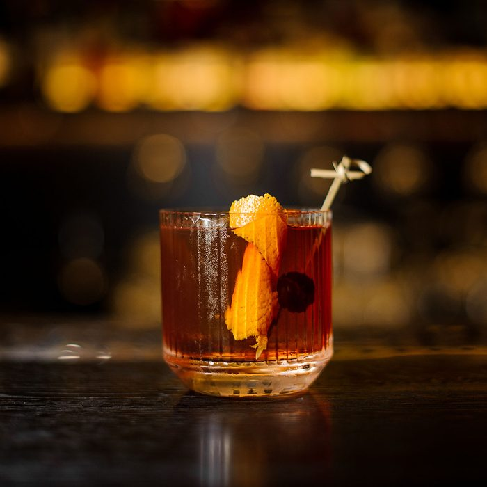 Glass of a Old Fashioned cocktail on the wooden bar counter on the blurred background