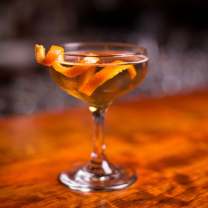 Low angle closeup of gourmet old fashion martini drink in champagne saucer cocktail glass filled with bourbon and brandy garnished by delicately spiral orange peel on red cherry wood grain countertop