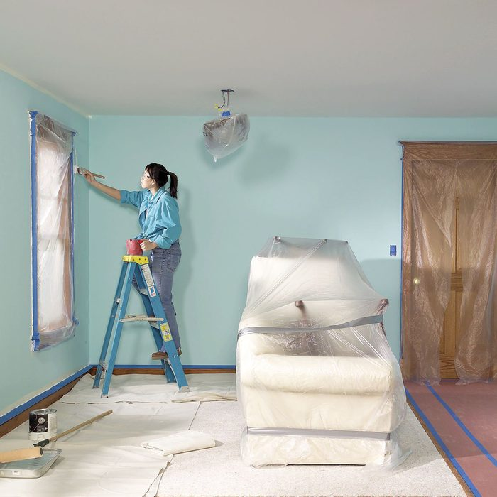 Woman on a ladder painting a room blue