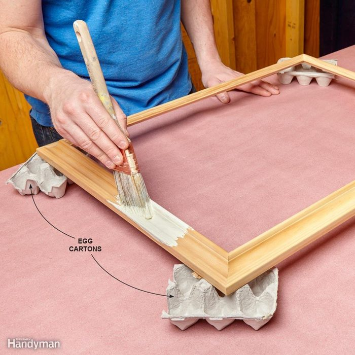 Using egg cartons to hold up a frame being painted