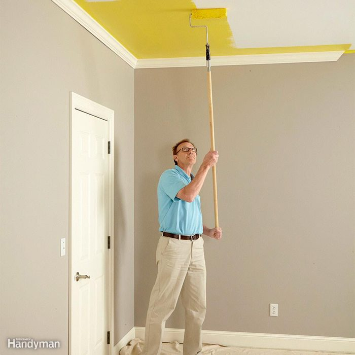 Painting the ceiling yellow with a long roller