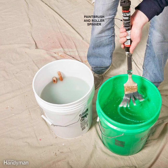 Cleaning a brush in a large green bucket of water