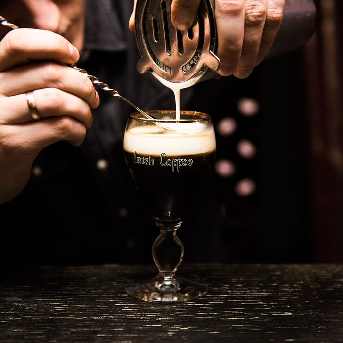 Irish Coffee cups with cream on a dark background