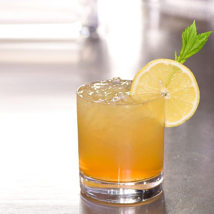whiskey lemonade sour based cocktail drink decorated lemon mint on bar counter