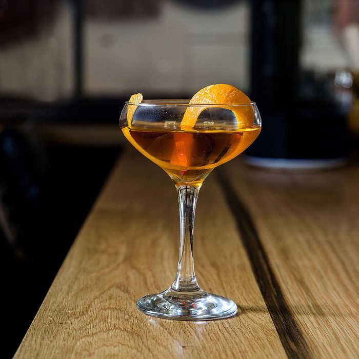 Classic Manhattan alcoholic cocktail served in a glass with a slice of orange peel