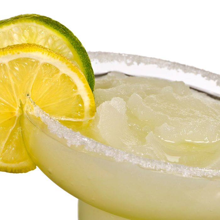 A Golden Margarita with a lemon and a Lime on the SIde Isolated