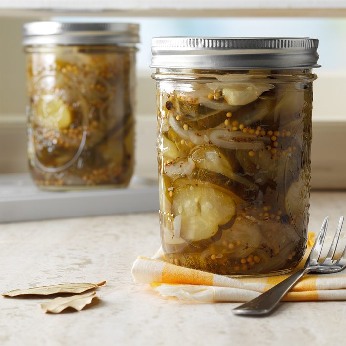 two jars of the best pickles recipe with a napkin, fork and bay leaves