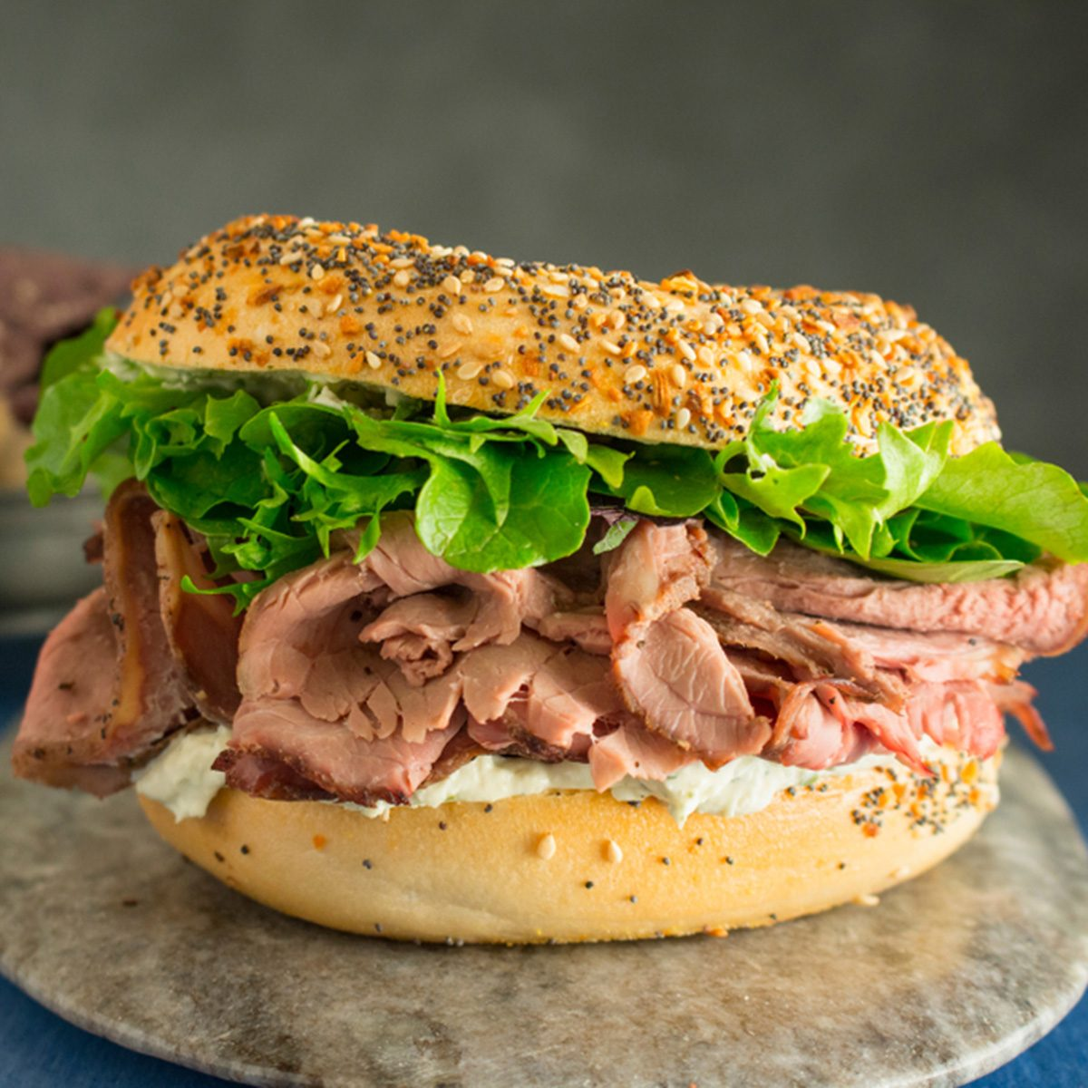 Roast beef sandwich with lettuce on an everything bagel with a side of blue corn chips