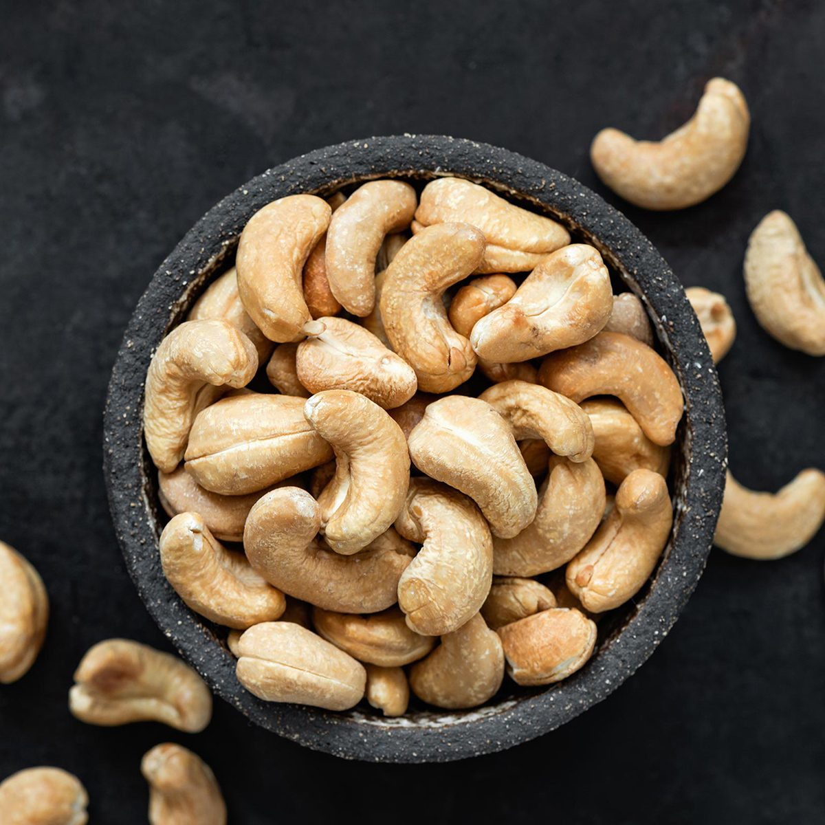 Cashew nuts in bowl on black background.