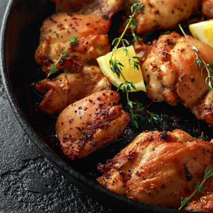 Roasted boneless skinless chicken thighs in lemon and thyme dressing served in vintage cast iron skillet