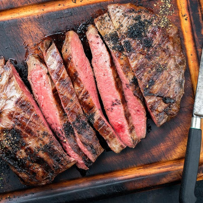 Barbecue dry aged wagyu flank steak sliced as top view on a burnt cutting with a knife