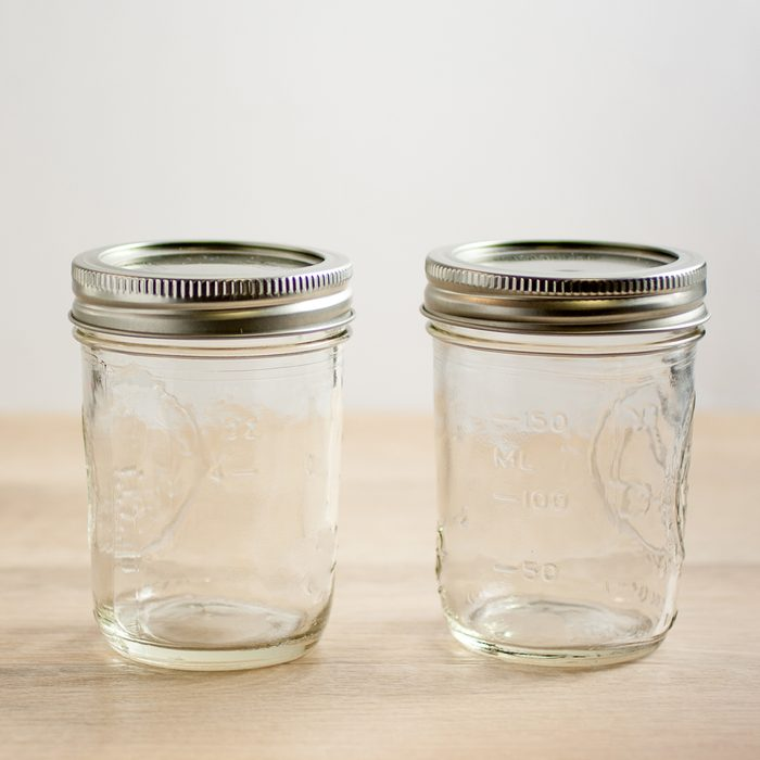 Empty canning jars await use on a wooden table.