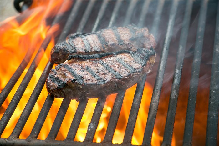 Beef steaks on the grill over wood fire